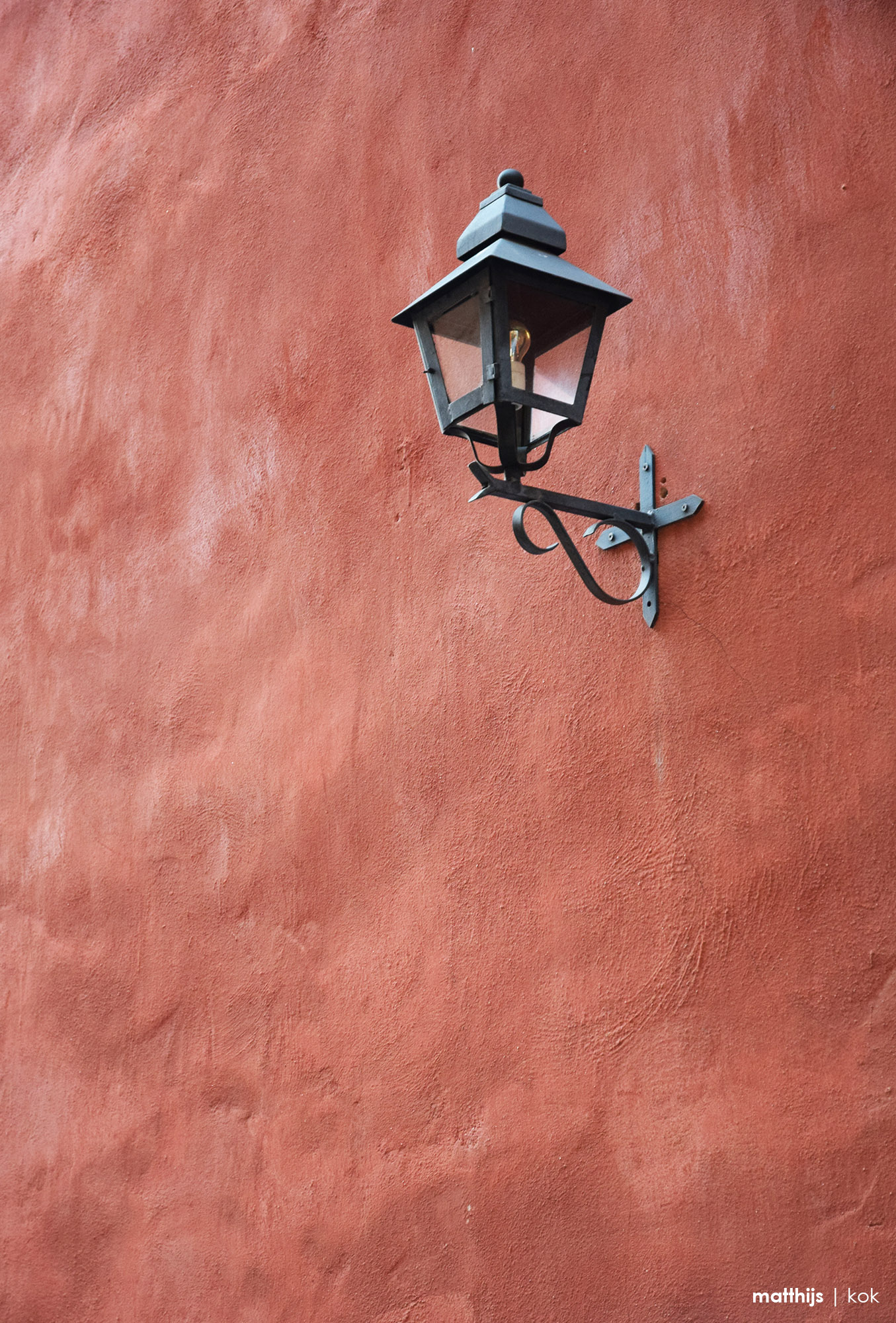 Old lantern on building wall in old town, Gamla Stan, Stockholm, Sweden | Photo by Matthijs Kok