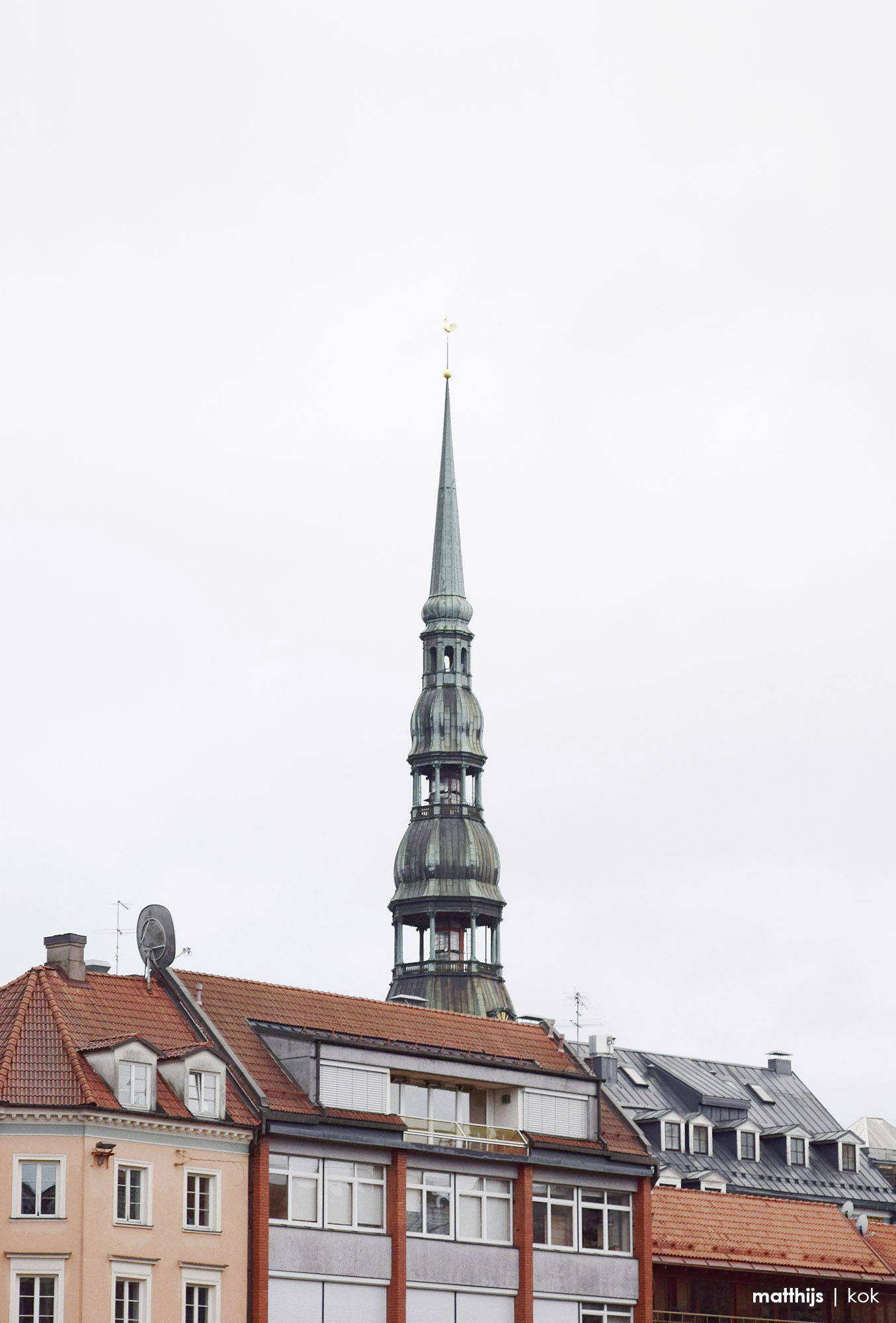 The spire of St. Peter's Church towering above the red clay and blue metal roofs of Riga Old Town, Latvia | Photo by Matthijs Kok